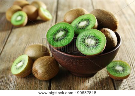 Juicy kiwi fruit in bowl on wooden background