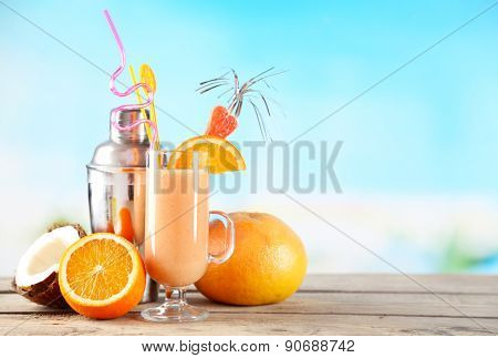 Glass of summer cocktail on wooden table on bright blurred background