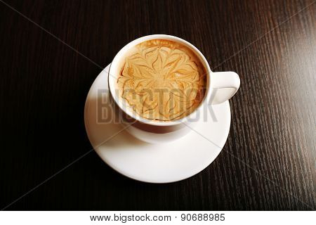 Cup of latte on wooden background