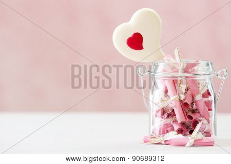 Jar of papers with sweet heart on table on bright background
