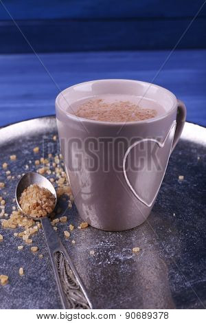 Cup of cocoa with spoon of sugar on metal tray on color wooden background