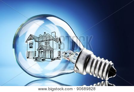 Light bulb with house sketch project inside on blue background