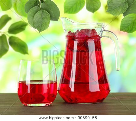 Pitcher and glass of compote on wooden table on nature background
