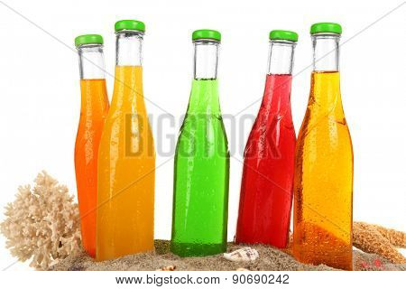 Bottles of tasty drink on sand close up