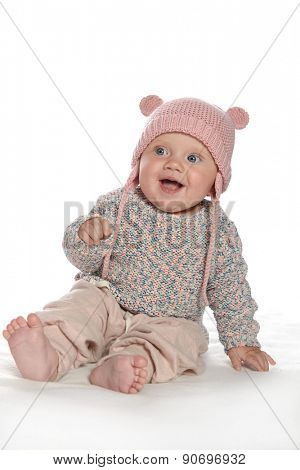 baby girl child sitting down on white blanket smiling happy pink fashion portrait face studio shot isolated on white caucasian  hat warm cloting