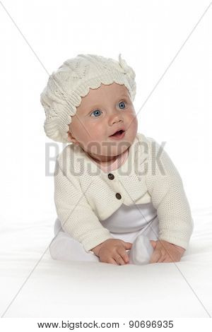 baby girl child sitting down on white blanket smiling happy in white warm clothing hat fashion portrait face studio shot isolated on white caucasian