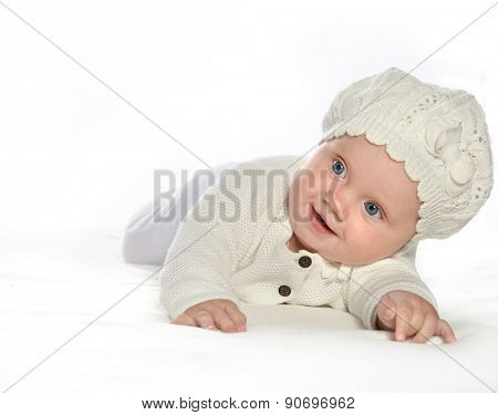 baby girl child lying down on white blanket smiling happy  fashion portrait face studio shot isolated on white caucasian  hat warm cloting