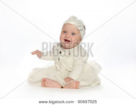 baby girl child sitting down on white blanket smiling happy white dress fashion portrait face studio shot isolated on white caucasian