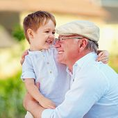 stock photo of grandpa  - portrait of happy grandpa and grandson embracing outdoors - JPG