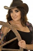 pic of cowgirl  - a cowgirl with her hand on the wagon wheel with a smile - JPG