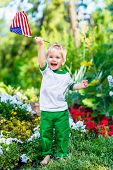 foto of waving  - Barefoot little boy with blond hair laughing and waving american flag in sunny park or garden on summer day - JPG