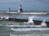 stock photo of outer  - Impelled by strong winds incoming waves splash against the piers which mark the entrance of the St. Joseph River into Lake Michigan. A catwalk the St. Joseph Lighthouse and its outer light can be seen on the north pier. 