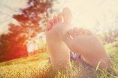 pic of barefoot  - Barefoot person lying on green grass outdoors - JPG