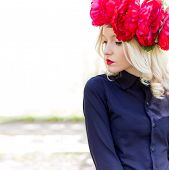 picture of woman red blouse  - beautiful young gentle elegant young blond woman with a red crown of peony in a black blouse walks in the lush apple orchard - JPG
