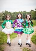 stock photo of cross-dress  - Three young beautiful girls in irish dance dress and wig posing outdoor - JPG