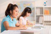 picture of schoolgirl  - Asian preteen schoolgirls writing test in classroom - JPG