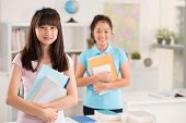 stock photo of schoolgirls  - Portrait of Asian schoolgirl with textbooks smiling and looking at the camera - JPG