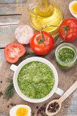 foto of pesto sauce  - sauce of pesto near a tomato olive oil and eggs in a studio - JPG