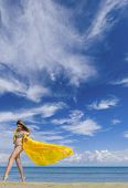 image of windy  - Young woman in bikini holding a yellow sarong on windy beach - JPG