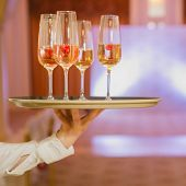stock photo of serving tray  - Waiter serving champagne with strawberries on a tray - JPG