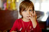 pic of licking  - little girl in cafe licking her fingers after meal - JPG