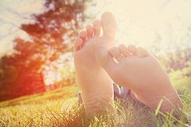 picture of barefoot  - Barefoot person lying on green grass outdoors - JPG