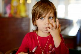 pic of finger-licking  - little girl in cafe licking her fingers after meal - JPG