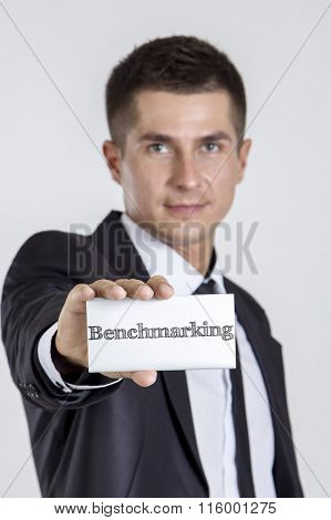 Benchmarking - Young Businessman Holding A White Card With Text