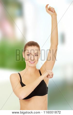 Woman applying antiperspirant.