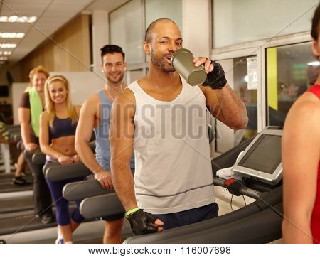 Happy guy drinking refreshment, smiling, training in gym.