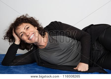A Woman Smiling  Her Legs Raised And Relaxing