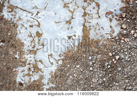 Frozen puddle and dirt road close-up
