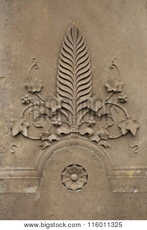 Palm leaf surrounded by ivy. Decorative architectural element.