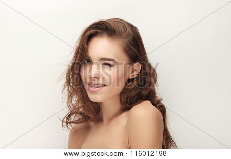 Closeup beauty portrait of winking young adorable brunette woman with trendy makeup posing with bare