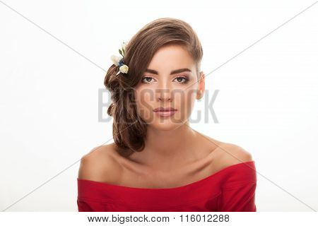 Young beautiful brunette woman in red blouse with low bun hairstyle and flower headpiece showing ado