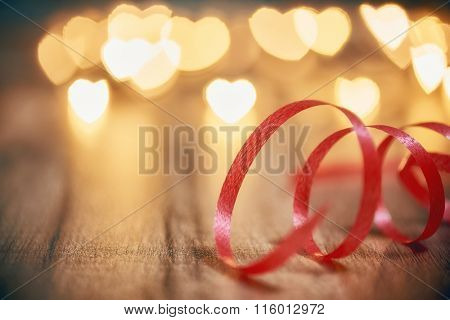 Garland lights on wooden rustic background. Valentine's day background with red ribbon and hearts. The concept of love and Valentine's day.