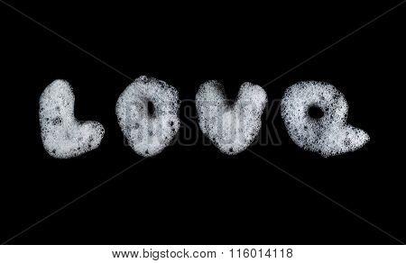 Word Love written soap foam bubbles. Figure lather, suds, shower texture and pattern. Black backgrou