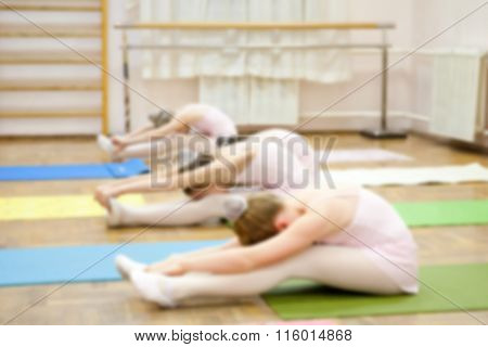 Training young ballerinas in ballet studio. Young dancers performing gymnastic exercise while warmin