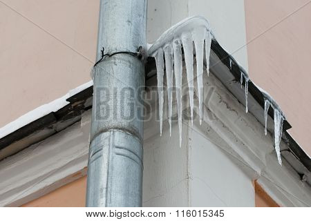 Natural icicles hanging near water pipe tube at roof. soft focus