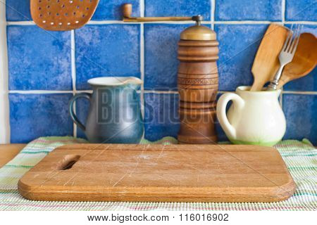 Still life with kitchen accessories. Green jug, hand grinder, vintage wooden spoons, cutting board o
