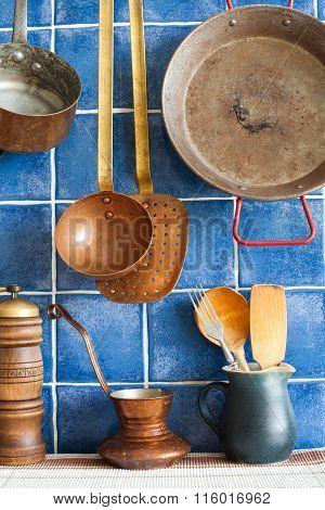Retro style copper utensils, coffee pot, crock, wooden spoons. blue tile background