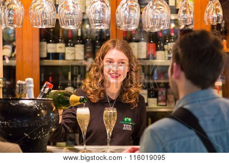 Waitress serving champagne at San Miguel market, Madrid.