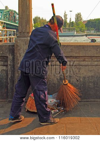 man is sweeping outdoor in Bangkok, Thailand