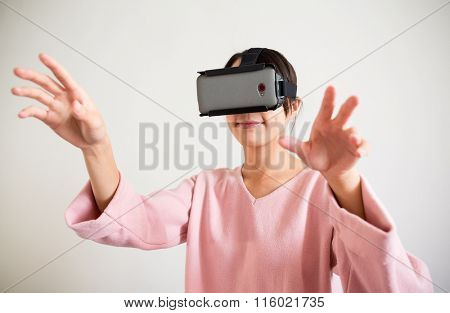 Asian Woman looking though vr device and hand want to touch something