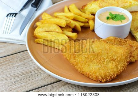 Crumbed Fish And Chips On Wooden Table