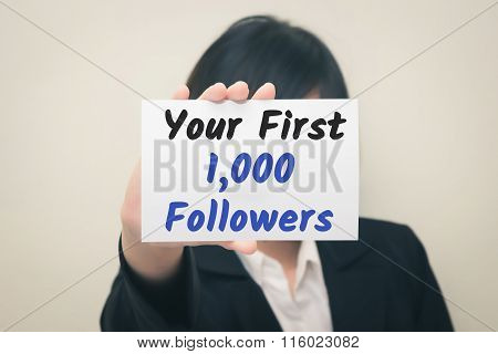 your first 1000 followers message on the card Held by women.