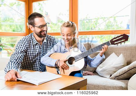 Father and daughter learning play the guitar, making music together