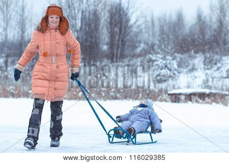 The Young Beautiful Girl With The Small Child The Son On A Sledge
