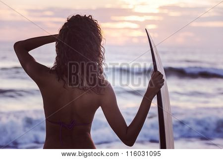 Instagram filter style rear view of beautiful sexy young woman surfer girl in bikini with surfboard on a beach at sunset or sunrise