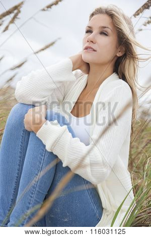 A beautiful blond woman or girl wearing jeans sitting in tall grass on a beach